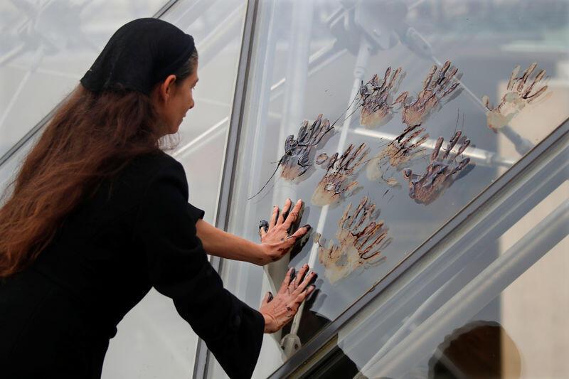 نشطاء يلطخون هرم اللوفر الزجاجي بالعسل الأسود احتجاجا على أنشطة توتال