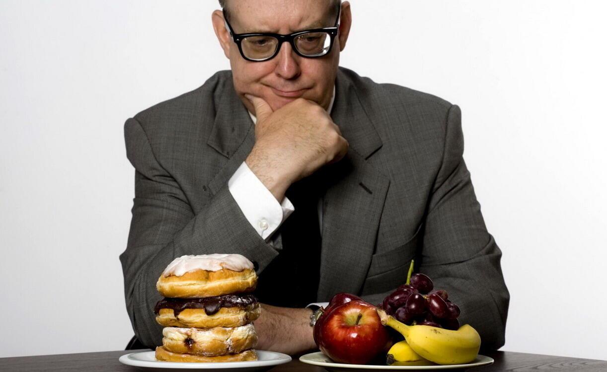 Man contemplating eating healthy or unhealthy food, studio shot